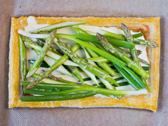 Stek bunnen ved 200 grader i ca. 10 minutter, eller til fyllet har blitt gyllent og kanten har hevet seg og fått litt farge. Hell forsiktig over resten av fyllet og legg på vårløk og asparges. Stek terten videre i ovn i ca. 20 minutter.
