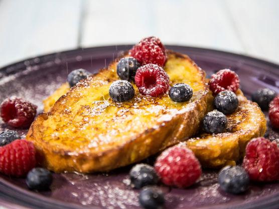 Legg de ferdigstekte arme ridderne på en tallerken, dryss litt honning over og pynt med friske bær. Et dryss melis helt til slutt blir ekstra fint!