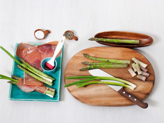 Skjær vekk de nederste 2 cm av asparges og rens vårløk, surr med skinke, pensle med olje og grill eller stek dem i ca. 4-6 min. Server samlet med aioli ved siden.