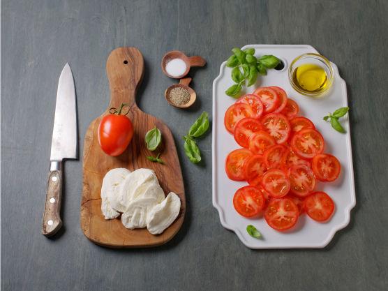 Skjær tomater og mozzarella i skiver og anrett med basilikumblader på et fat og drypp over olivenolje. Server kyllingboller med dressing og tomatsalat.