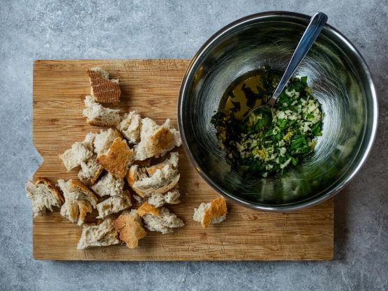 Riv brødet i store biter. Finhakk hvitløk og basilikum og riv sitronskallet før du presser sitronen. Bland brødet med blandingen.
