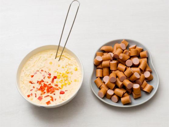 Visp sammen fløte, egg og pesto, vend inn pølsebitene, godt avrent mais, grønnsaker og ost.