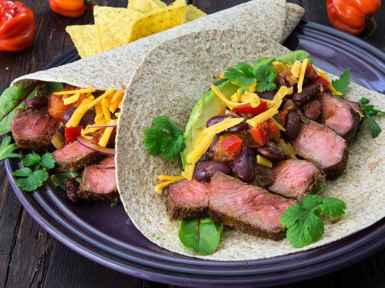 Fyll tortillaen med salat, skiver av biff, avokado i skiver, chilibønner og revet cheddar på toppen. Pynt gjerne med mer frisk koriander.