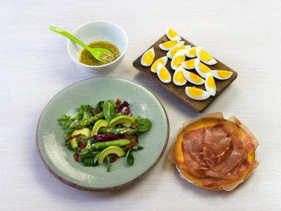 Anrett salat, avokado, tomater og asparges på tallerkener, og topp medserranoskinke og egg. Ha over dressing og server.