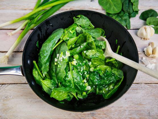 Fres spinat, eller finstrimlet grønnkål, sammen med finhakket hvitløk og vårløk til det faller sammen.