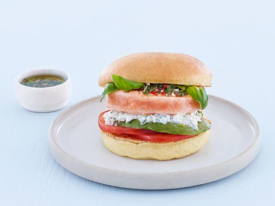 Anrett først tomatskiver og grillet avokado på brødet. Legg så på et par blader basilikum og en raus skje med tzatziki.