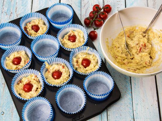 Fyll muffinsformene og stikk en cherrytomat ned i midten av hver muffin.