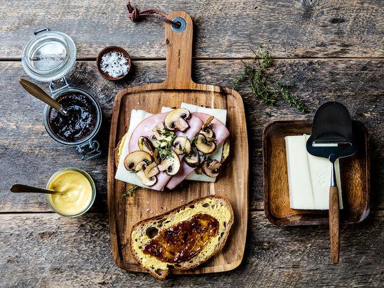 Smør fikenmarmelade og sennep på brødskivene. Legg ost, skinke og sopp på den ene skiven og topp med den andre brødskiven.
