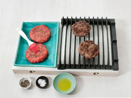Pensle burgerne med olje, krydre med salt og pepper og grill eller stek hamburgerne på sterk varme, ca. 5 min. på hver side.