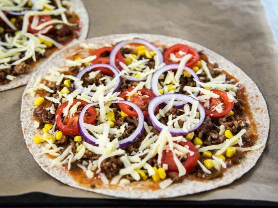 Legg tortillaene på bakepapir på et stekebrett. Fordel tacosaus, kjøttdeig, mais, tomatskiver, rødløk og ost på hver tortilla.
