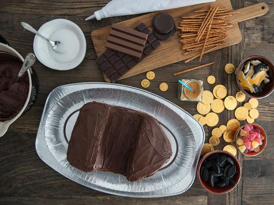Smør sjokoladeglasur rundt hele kaken og for å feste bitene av kaken til hverandre.
