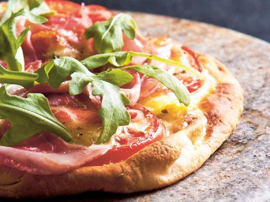 Fordel tomatsaus på bunnen før du legger på løk og mozzarella. Ringle over en god olivenolje. Stek pizzaen på 250 °C i 8-10 minutter, eller til pizzaen har en gyllen farge og sprø bunn. Fordel parmaskinke, høvlet parmesan, oliven og rucculasalat over.