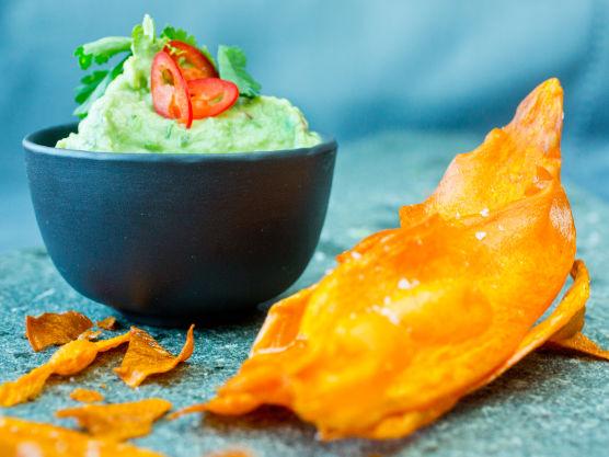 Del avokadoen, fjern steinen og skrap ut kjøttet. Mos kjøttet med en gaffel og bland inn limesaft, rømme, hvitløk og chili. Smak til med salt og rør inn koriander om ønskelig. Dekk til overflaten med plastfilm og la guacamolen hvile i kjøleskapet frem til servering. Lar du stenen ligge i guacamolen holder den seg grønn lengre.