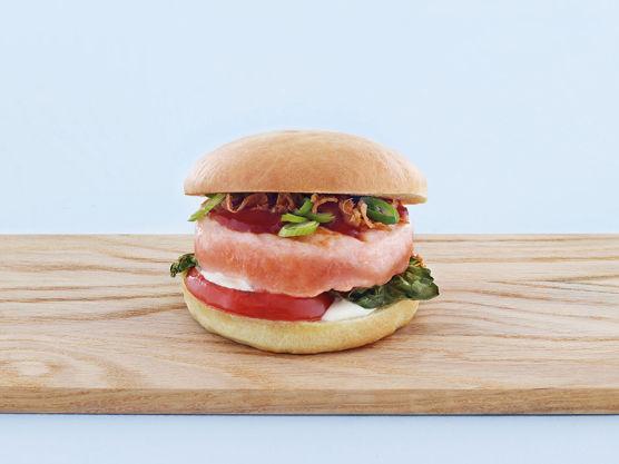 Legg så på lakseburger og pensle med BBQ saus. Topp med rømme, snittet vårløk og sprøstekt løk.