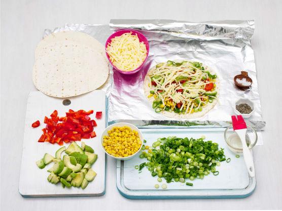 Pensle 4 store stykker aluminiumsfolie med olje. Legg 4 tortillas på foliestykkene, fordel ost og grønnsaker på tortillaene, og krydre med salt og pepper. Topp med 4 nye tortillas.