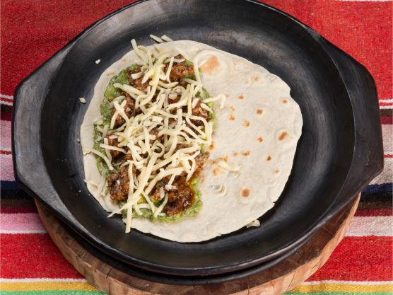 Smør et lag med guacamole på den ene halvdelen av tortillaene. Ha karbonadekjøttet over og dryss revet ost på toppen.