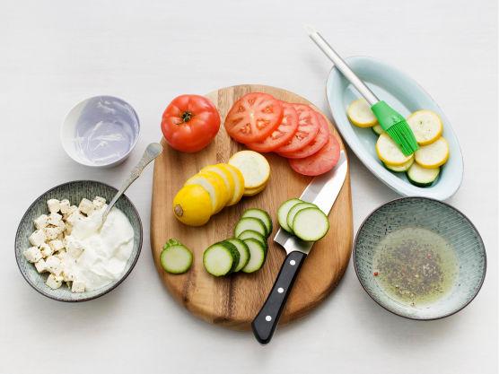 Hell oljen av fetaosten, og sett oljen til side. Mos osten med en gaffel og bland med yoghurten. Skjær tomater og squash i skiver og pensle med oljen fra fetaosten.