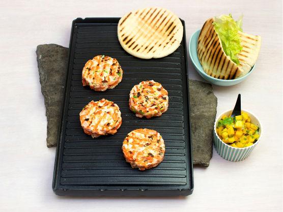 Varm pitabrødene på grillen eller i stekeovnen på 200 °C. Lag et snitt i brødene og fyll med salat, lakseburger og mangosalsa.