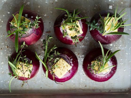 Sett løkene over i en passende ildfast form. Topp hver løk med en smørklatt, en liten urtekvast og et saltdryss.