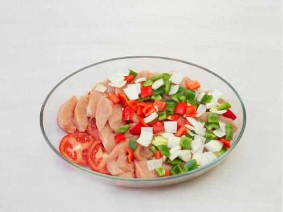 Skjær løk og paprika i terninger og tomat og kylling i skiver. Dekk bunnen i en smurt ildfast form med tomatskiver, ha i kyllingskivene og topp med løk og paprika.