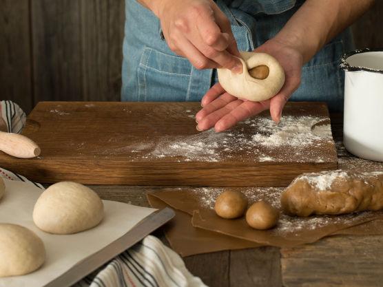 Pepperkakedeigen rulles ut i små kuler. Rull så bollene og fyll med pepperkakedeig kuler i midten. Pass på å lukke bollen ordentlig.
