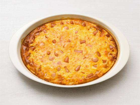 Smør en vid ildfast form, fordel blandingen i formen og stek i ovnen på 220 C i ca. 25 min. til den er gyllen og fast. Dekk med aluminiumsfolie mot slutten av steketiden om retten blir for mørk.