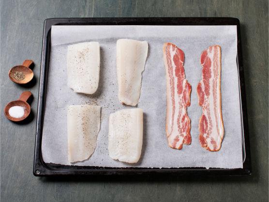 Del torsken i fire biter, krydre den med salt og pepper og legg fisk og bacon på en stekeplate. Bak i ovnen på 200 °C til fisken er gjennomstekt og baconet sprøtt, ca. 10-12 min.