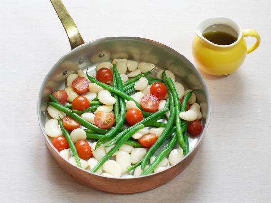 Ha i avrente bønner i pannen og stek til alt er gjennomvarmet. Vend inn dressingen og topp med biter av grillet kylling.