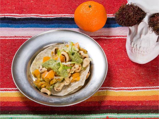 Ha litt salat på tortillaene, kjøtt, terninger med klementiner, og deretter striper med grønn salsa på toppen.