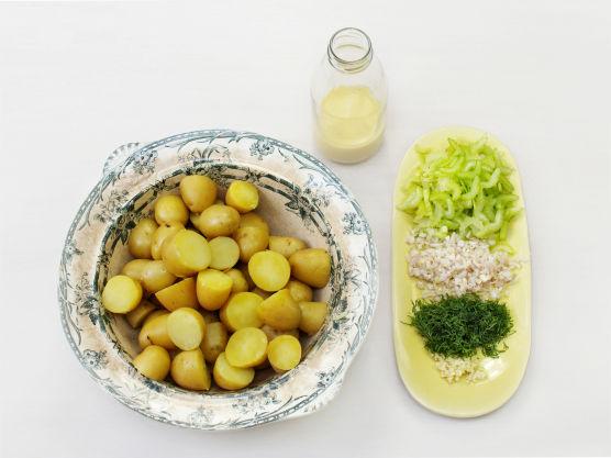 Del potetene i biter, hvis de har tynt skall trenger de ikke å skrelles. Hakk selleri, løk, hvitløk og dill, og bland med potetene. Vend inn dressingen mens potetene er varme.