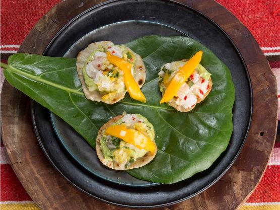 Legg godt med gul salsa i bunnen av de sprø tortillaene, litt av fisken over, og topp med guacamolekrem og en skive mango. Klar til servering.