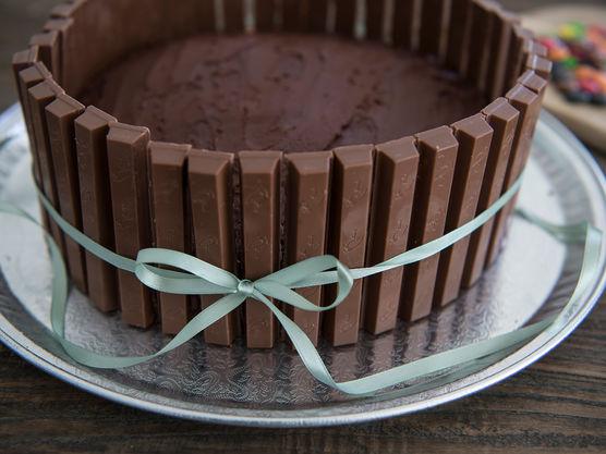 Del kvikklunsj sjokoladene i staver og sett langs kanten rundt hele kaken. Bind fast med et vakkert bånd for å holde dem på plass.