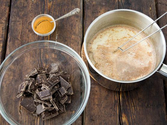 Knekk sjokoladen i biter i en bolle som tåler god varme. Kok opp melk, fløte, sukker og kanel.