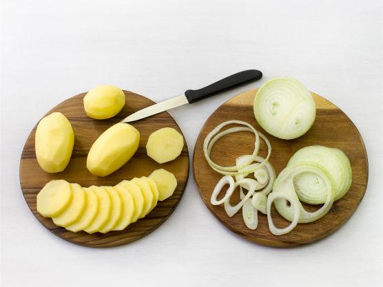 Skrell og skjær poteter og løk i tynne skiver. Rens og del fisken i biter på ca. 5 cm.