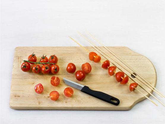 Kok pasta etter anvisning på pakken. Del tomatene i to, tre dem på spyd. Rist pinjekjerner i en tørr stekepanne.