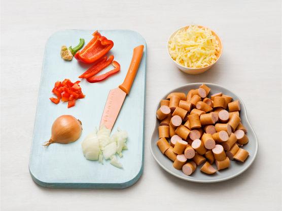 Rens og skjær grønnsakene i terninger. Riv ost og skjær pølsene i biter.