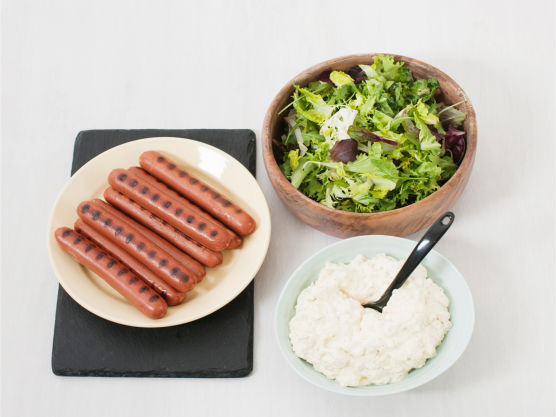 Anrett salaten på serveringsfat, topp med pølsebiter og saus, og server.