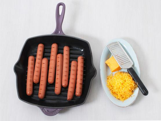 Riv osten. Grill eller stek pølsene på sterk varme, ca. 8 min.