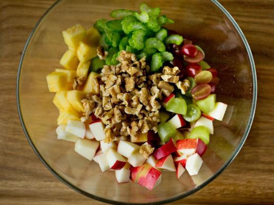 Skjær epler og ananas i jevne terninger og del druene i to. Fjern de groveste trevlene på stangsellerien og skjær i tynne skiver.