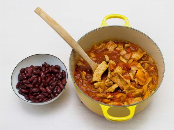Tilsett krydder, hakkede tomater og kraft. Kok opp og la koke i ca. 20 min. Ha i avrente bønner, varm opp og smak til med salt og pepper.
