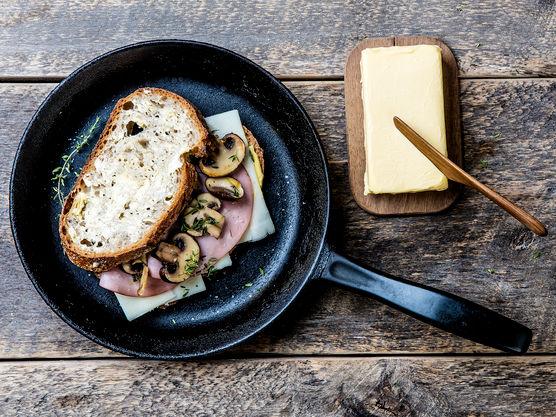 Smør sidene som vender ut med smør og stek i en stekepanne på middels varme under lokk til skiven er gyllen. Snu og stek videre til osten er smeltet.  Du kan også bruke et ostesmørbrødjern til å steke smørbrødet i om du har det.