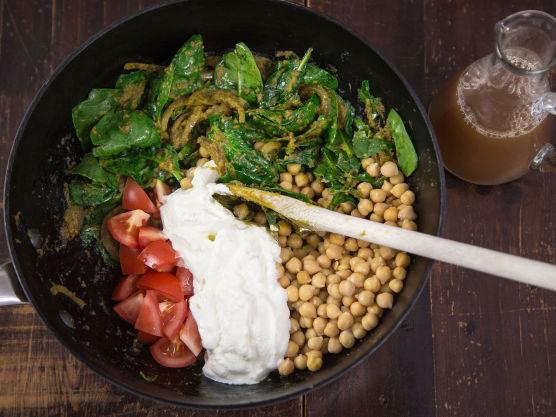 Tilsett spinat, tomat og kikerter. Stek til spinaten faller litt sammen og tilsett så yoghurt og kraft eller buljong. Smak til med salt og pepper.