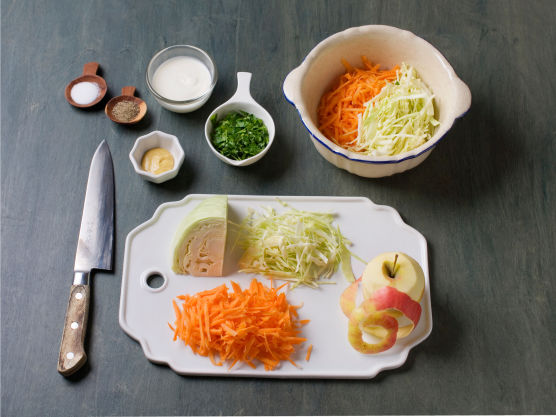 Finsnitt kål, skrell og riv gulrøtter og eple, og finhakk persille. Bland inn Skyr og sennep, og smak til med salt og pepper.