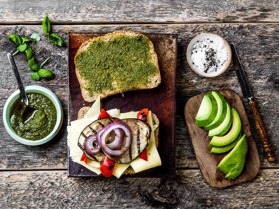 Legg grillede grønnsaker, avokado og ost på den ene skiven og topp med den andre, pesto-sidene mot hverandre.