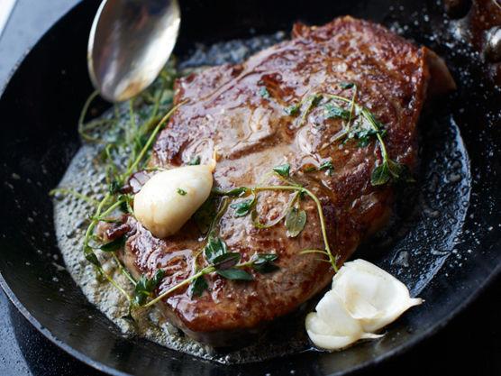 Skru ned varmen. Ha i smør, knust hvitløk og timian. Øs stekesmøret over biffene jevnlig og la dem ligge og «kose» seg ismøret til de er stekt slik du vil ha dem.