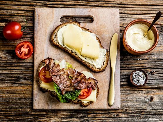 Smør aioli på begge skivene. Legg tre skiver ost på den ene skiven og topp med tomatskiver, salat og sprøstekt bacon. Krydre med salt og pepper.