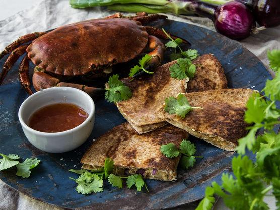 Fordel krabbekjøttet på tortillalefsene og strø over revet ost. Brett lefsene i to og stek dem olje til de er gyllne og osten har smeltet.