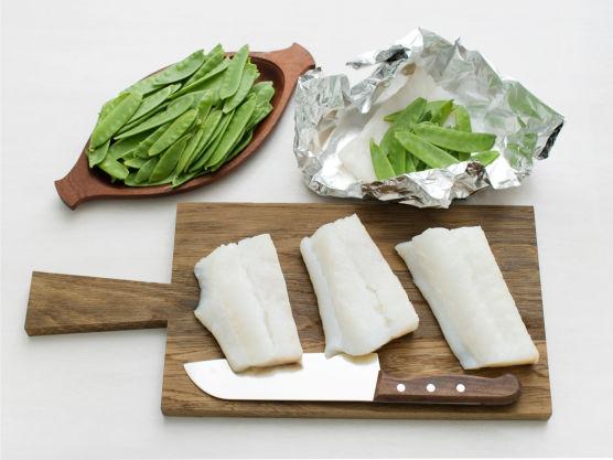 Rens og del fisken i serveringsstykker. Legg fisk og sukkererter på et sykke tykk aluminiumsfolie.