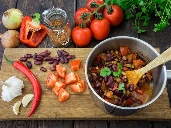 Hakk løk, hvitløk, chili og paprika i små terninger. Fres dem sammen med tacokrydder i olivenolje til de er blanke. Grovhakk plommetomatene og tilsett disse til gryten sammen med bønner. La det hele småkoke til tomatene har gått litt i oppløsning. Mos noen av bønnene med en gaffel for å tykne sausen. Tilsett finhakket frisk koriander og smak til med salt.