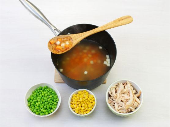Rens og riv kyllingen i strimler. Tilsett kylling, erter og mais og la koke i ca. 5 min.
